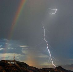 A rainbow and bolts of lightening are shown next to the Hollywood sign Wednesday Sept. 29, 2010 in L... - AP