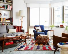 Eclectic apartment living room with layered rugs and colorful furniture