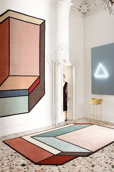 Each rug has an asymmetrical, abstract silhouette with an architectural style to it.