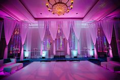 Fabric draping, chic uplighting, and lounge furniture create a party vibe in this reception space.
