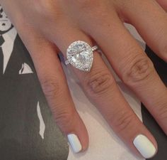 Oh dear holy moly. Huge pear shaped center stone with diamond halo and petite diamond shank in white gold engagement ring