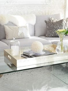 Lucite coffee table, xl gold tray, perfect accessories, light grey sofa.