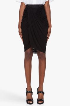 Black Draped Backpack Skirt 21187F117002 Draped skirt in black. Tonal leather trim, plastic d-loops and elastic banding at waist. Concealed zip and hook-eye closure at rear. Angled hem. Tone on tone stitching.