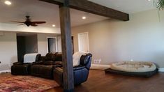Elegant finished basement beams created with faux beams placed over existing support structures.