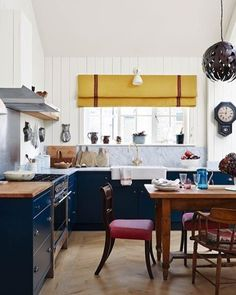 Open-plan living is made cosy with warm touches in this mews house in London owned by designer #CarolineRiddell. In this kitchen traditional and contemporary pieces work together. Carrara-marble-topped units are painted in 'Hague Blue' by @farrowandball while a mustard blind from @susandeliss brings warmth to the space.  @lucasallenphoto  #interiors #design #decoration #kitchen