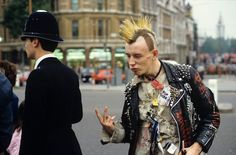 PUNK GIVING THE V SIGN TO A POLICEMAN, LONDON, 1983 – NILS JORGENSEN/REX