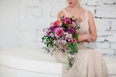asymmetric cascade bridal bouquet with purple Japanese scabiosa, purple hellebores, Silvery Moon Japanese sweet pea, Charlotte ranunculus, peach ranunculus, jasmine vine and blue star fern, accented with vintage velvet and grosgrain cascading ribbons.  Photo by Leah Barry Photograpy, flowers by Floral Verde LLC Cincinnati, Ohio.