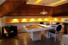 Na Sala de Games, projetada por Renata Mueller para a Casa Cor Paraná 2011, a madeira no piso e nas paredes aquece o ambiente moderno de iluminação aconchegante. No centro, a mesa de sinuca se transforma em mesa de jantar com a colocação de um tampo em laca branca – uma boa ideia para ambientes multiuso.