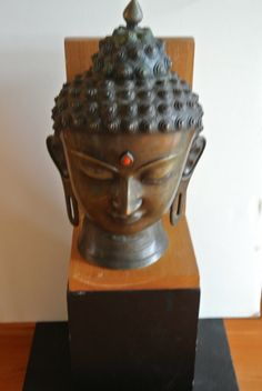 Vintage Bronze Buddha head statue on wooden by vintageARTifax