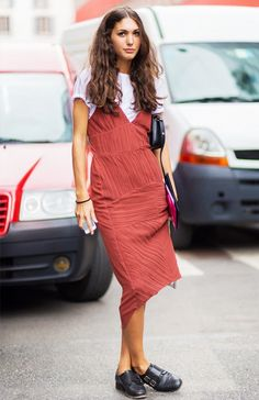 A white t-shirt is layered underneath a muted red tank dress and worn with black oxfords and a black bag
