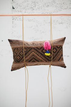 "this brown wool laotian textile makes for one dreamy pillow. the geometric patterns in tones of brown pair well with a soft pendleton ecru wool backing. the pillow is finished with an indian camel saddle tassel or ""swag."" saddle tassels are traditionally used for both utilitarian and decorative purposes. this tassel is mostly pink, with a bit of blue and yellow. pillow measures 16""x23"". zipper closure. feather/down fill.perfect for the modern, world-inspired ..."