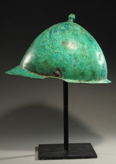 With hemispheric calotte topped by a mushroom-shaped knob, a wide brow brim and a narrower brim at the back. Attractive green patina. Derived from Etruscan models, this served as the primary helmet of the late Republic.  1st Century BC  H. 7 1/4 in.