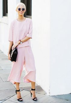 Dannon K Collard of Like the Yogurt wears matching pink top and culottes with black strap sandals, a black oversized clutch, circle sunglasses and a watch.
