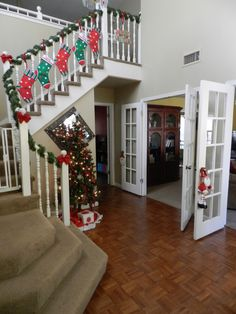 Decorating with littles for Christmas by stockings on the staircase, tree in the hallway and hanging santa's on the doorknobs.#christmas #staircase #doors