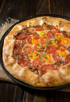 This herbed tomato galette with Parmesan crust is a delicious use of summer tomatoes and herbs. A buttery, flaky crust is flavored with fresh Parmesan cheese then filled with sweet tomatoes, gruyere cheese, basil and rosemary for a free-form, rustic and delicious galette.
