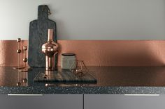 An eclectic mix of crockery and utensils in copper, slate and grey tones complete the modern look of this kitchen. Greenwich Gloss Slate Grey from the Universal Collection by Howdens Joinery.