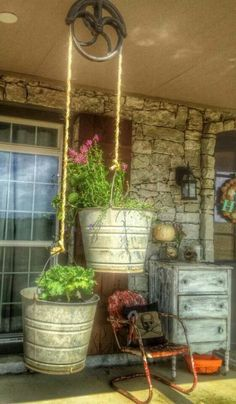 Pulley System for Flower Pots or Herb Plants on the Front Porch: cool!! Love this! Hang one bucket (or pot) from each side of the pulley. Use buckets or pails for the rustic farmhouse look. Front porch, back porch, pergola, even inside in kitchen for herb plants, different way to hang flower pots. Farm, Barn, Wood, Stone & Steel(love for rustics)