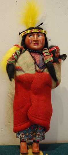 Beautifully adorned vintage Skookum doll robed in red and green, cream and navy camp blanket wrap around her, her baby and over her calico dress. luckystargallery.com $265