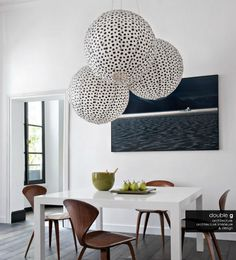Giant poppy paper lights by Paola Navone hang above a white lacquer table that was conceived, drawn, and produced by the owner of Where I'd Stay's St Honoré flat.