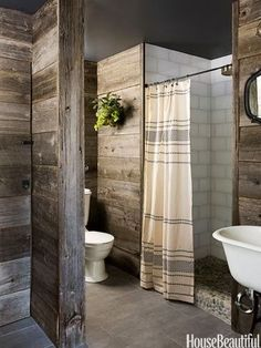 Love the wood planked walls, pebble shower base and grain sack shower curtain.