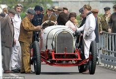 Ready to race: Extras in vintage overalls stand beside a classic racing car