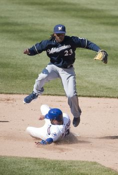 6/`162 - Cubs 8, Brewers 0 - Second baseman Rickie Weeks #23 of the Milwaukee Brewers leaps over David DeJesus #9 of the Chicago Cubs as he turns a double play on a ground ball hit Darwin Barney during the sixth inning (4/12)