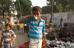A young boy gets a cup of tea, while healping his father set up his stall in the Baroda Friday Market.