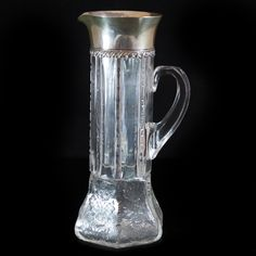 "DESCRIPTION: Tiffany & Co. sterling and crystal pitcher. Features a hexagonal base etched with floral designs tapering up to a slimmer neck of fine crystal cut garnish. Finished with a sterling silver overlay lid marked: Tiffany & Co, Makers Sterling Silver"" CIRCA:20th Ct. ORIGIN:USA DIMENSIONS:H:11"" Diameter:4"""