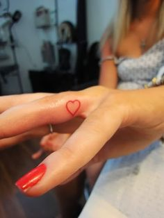 Red heart finger tattoo. I want this but with a sacred heart