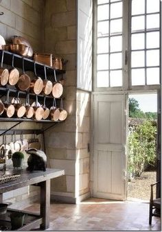 what a beautiful kitchen, look at that big door, and all those copper pans
