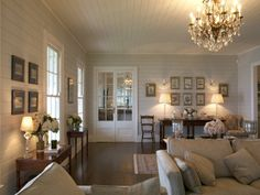 family room in Australian farmhouse with rustic wide-board flooring and timber-lined walls and ceiling / REA Group