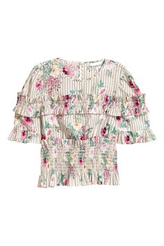 Een kortere blouse van geweven katoen met een geprint dessin en smokwerk met een volantrand boven en onder. Het model heeft een splitje met een knoop in de