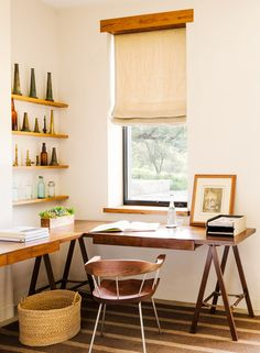 Wall art with sculptures and bottles, wood desk, wood chair, woven basket, and a brown and tan striped rug