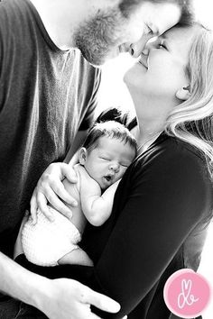 newborn and parents pose