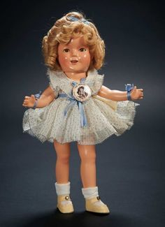 "Shirley Temple owned this Ideal Composition Shirley Temple doll in Original ""Curly Top"" Costume 13""  All composition with socket head, hazel sleep eyes, impressed dimples, lashes, open smiling mouth, four teeth, mohair blonde ringlet-curled wig, jointing at neck, shoulders & hips. Wearing her original crisp organdy pleated dress with blue polka dots & ruffled collar, trimmed with blue sash, wrist ribbons, & hair bow, one-piece undergarment, socks & shoes, and with celluloid pin. Z"
