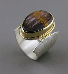 "When asked how she finishes her bezels, Janet Alexander said: ""I use a couple of rubber wheels on the flex shaft. First I file the join smooth, then hit the bezel with a 320 grit barrel sander, smooth around the stone with a pumice wheel. It is very soft and will not harm the stone. Then I use 220 grit gray silicone cylinder, followed with a 800 grit green silicone cylinder wheel. After that I polish using Bobbing compound on the buffing wheel and then finish off with Fabuluster."""