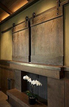 TV and Fireplace: Lots of ideas for TVs over fireplaces. This one uses barn door hardware and wooden panels.