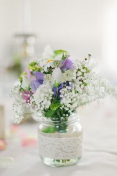 Pretty table flower arrangement with lace on the vase, photo by 2 Brides Photography | junebugweddings.com