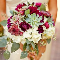 A vibrant, textured bouquet of dahlias, succulents, ranunculus, eucalyptus, and scabiosa pods aligned perfectly with the vintage feel of the day.