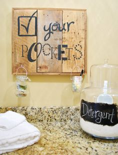 "This Check Your Pockets sign in the laundry room of the ""European Elegance"" home (with jars to stash change, pens, candy, and money before they go into the washer) is a cute functional idea. Plus it's inspiration to make sign art from scrap wood with any message stenciled on the front."