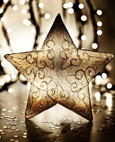 Image of 'Star, Christmas tree ornament, golden decoration over blur lights