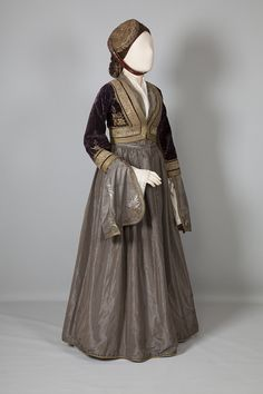 """""""Amalia"""" Costume from Athens (late 19th Century). The urban costume of the Peloponnese spread to other parts of Greece after 1837 when Amalia, the first Queen of Greece, adopted it as the official court dress. Made of taffeta with an open bodice to show the neck opening of the chemise.The cap is a Kalpak (Kalpáki). Married women wore a tasselled flat round cap (Féssi) which they covered with black lace when they went to church.."""