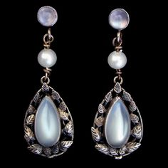 This is not contemporary - image from a gallery of vintage and/or antique objects. BERNARD INSTONE (1891-1987) (Attributed.)  A pair of Arts & Craft silver earrings. The central moonstone surrounded with  silver leaves suspended from wirework set pearls. The screw fittings also set with moonstones.