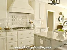 Faceted white subway tile with a basket weave tile framed with pencil tile feature over the stove top. Love it!