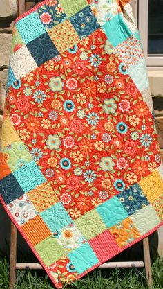 """This quilt was made with Block Party by Sandy Gervais by Moda Fabrics. This beautiful quilt includes red, orange, yellow, cream, navy blue, aqua and green. It measures approximately 38"""" by 43"""" perfect for that special little girl to cuddle with. The backing is a coordinating print from the line that features a beautiful floral pattern which makes this quilt reversible. This quilt is just as precious as can be!  This quilt was created with our very own Double Focus quilt pattern seen here…"""