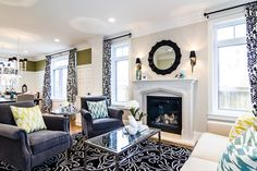 Visually Dividing Open Concept Living/Dining with moulding & paint, but tied together with matching drapes - Unrau Home by Lisa Clark Design via Houzz; Drapes by Tonic Living