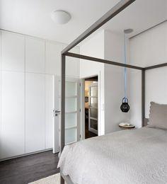 Bílá vestavěná skříň vhodně využívá celou plochu stěny a neruší kompaktnost prostoru. Vlněný koberec je z produkce firmy Voivo.