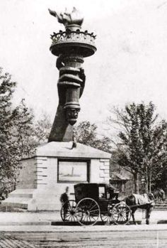 The arm and torch of the Statue of Liberty in Madison Square Park, New York.    These portions of the Statue were exhibited to raise funds for the completion of the statue and its pedestal.    The arm and torch remained in the park from 1876 until 1882.    Members of the public could pay fifty cents to climb to the balcony of the torch.