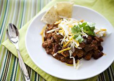 Nigella's Chocolate Chip Chili recipe - I love this recipe because I can put it together in minutes and then it goes in the oven (or you could transfer it to a slow cooker) for a few hours.  When the times rolls around to get the chili on the table, the kitchen has been cleaned up, the table is set, I've folded a few loads of laundry, and I have sat on the couch for a bit flipping through Us Weekly. #slowcooker #chili