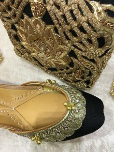 Black Jutti from the Maharani Jutti collection by Tyche London. These have ghungroo details and are lined with extra cushion for comfort. Paired here with a black and gold embroidered clutch bag.